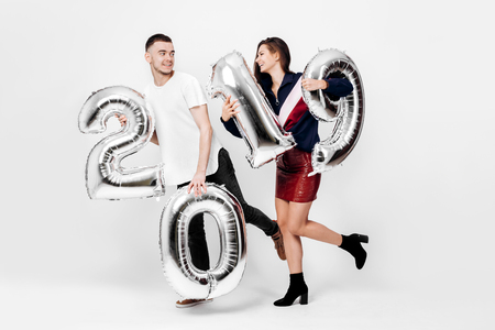 Funny girl and guy dressed in a stylish smart clothes are holding balloons in the shape of numbers 2019 on a white background in the studio