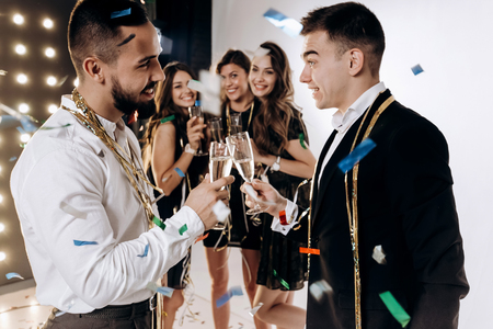 Beautiful young girls and guys dressed in stylish elegant clothes smile  together and clink glasses with champagne confiture around. Party time Banco de Imagens