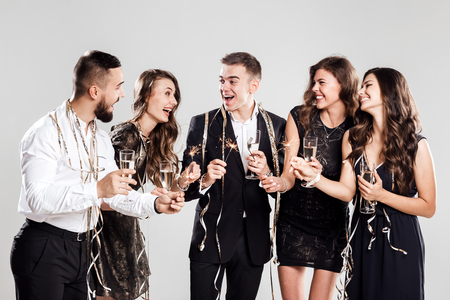 Company of  girls and guys dressed in stylish elegant clothes have fun together holding glasses of champagne and sparkles in hands on the white background confiture around. Party time