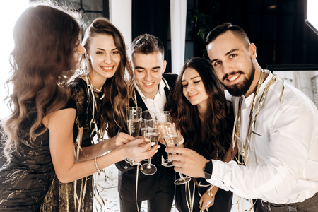 �¡ompany of beautiful young girls and guys dressed in stylish elegant clothes stand together and clink glasses with champagne. Party time Banco de Imagens