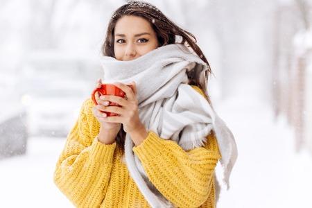 Schönes dunkelhaariges Mädchen in einem gelben Pullover und einem weißen Schal, das an einem Wintertag mit einem roten Becher auf einer verschneiten Straße steht