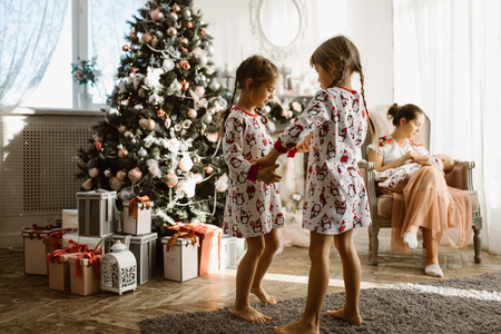 Two little sisters in pajamas having fun New Years tree with gi