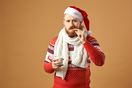 Red-haired man with beard dressed in a red and white sweater with deer, white knitted scarf and a hat of Santa holding a glass of milk and bites a cookie on a beige background