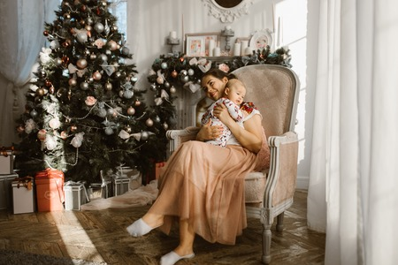 Beautiful mother sits in the armchair with her little baby next to the fireplace and  New Years tree with gifts in the light cozy room