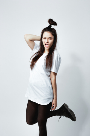 Young dark-haired girl with a funny hairstyle dressed in white t-shirt, black tights and shoes winks posing on the white background in the studio
