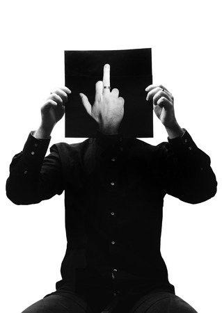 Black and white photo of man in the black shirt sitting and holding a photo with hand showing middle finger in place of his face