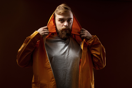 Guy with a beard and mustache dressed in a gray t-shirt and yellow jacket with a hood is standing on a brown background in the studio