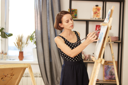 Charming drawing teacher in the beautiful dress shows drawing technique at the easel in the art studio
