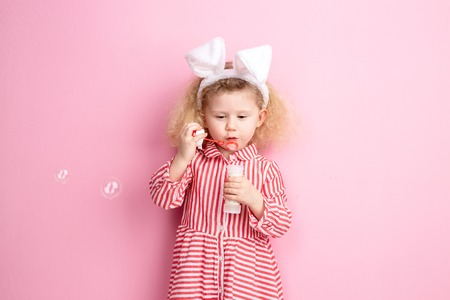 Lovely little girl in a striped red and white dress and bunny ears on her head inflates soap bubbles standing against a pink wall