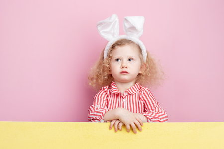 Funny little curly  girl in a striped red and white dress and bunny ears on her head stands  behind the yellow board against a pink wall Stock Photo