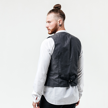 Handsome stylish man with beard and bun hairstyle dressed in gray vest over a white shirt and gray trousers poses in the studio on the white background