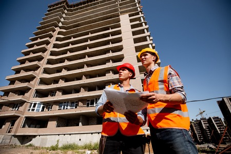 Two structural engineers dressed in shirts, orange work vests and helmets explore construction documentation against the background of a multistorey building Stok Fotoğraf