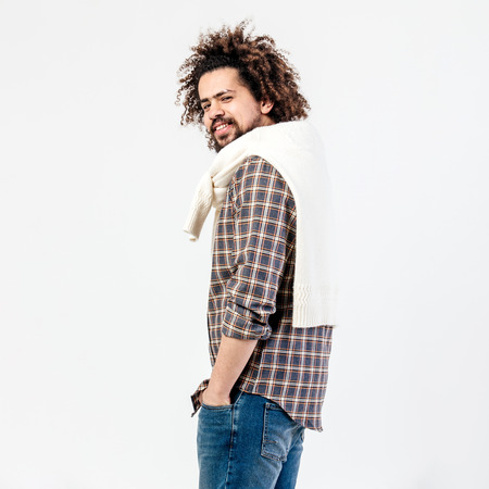 Brown-haired curly guy with a beard dressed in checkered shirt, jeans and white sweater draped over his shoulders poses in the studio on the white background.