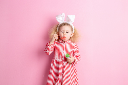 Pretty little girl in a striped red and white dress and bunny ears on her head inflates soap bubbles standing against a pink wall