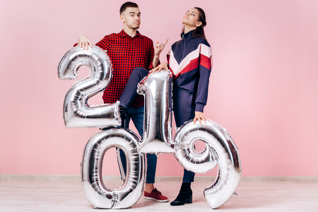 Funny friends girl and guy dressed in stylish clothes are holding balloons in the shape of numbers 2019 on a pink background in the studio Banco de Imagens