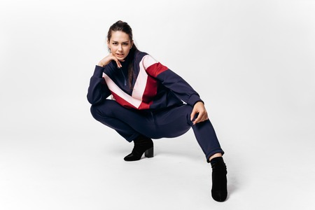 Nice girl dressed in sporty blue suit with a red and white print on a sweatshirt and heels poses squatting on the white background in the studio