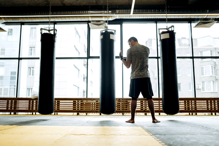 Dark-haired guy dressed in the grey t-shirt and black shorts  stands next to punching bags against the background of panoramic windows in the boxing gym