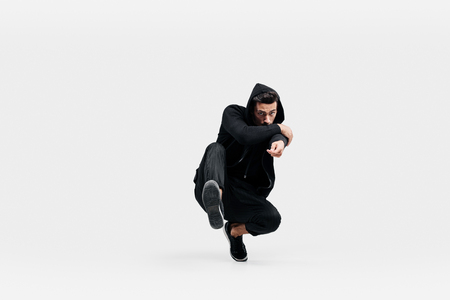 Handsome young dancer wearing a black sweatshirt and black pants is dancing breakdance doing dancing movements on the floor