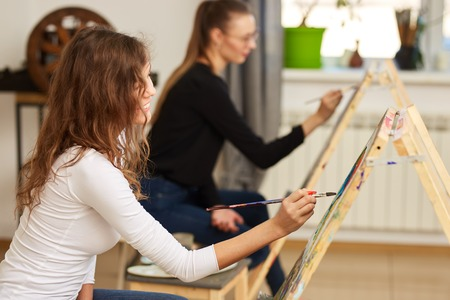 Girl with brown curly hair dressed in white blouse paints a picture at the easel in the drawing school