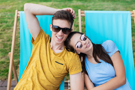 A beautiful couple in the sunglasses is lying on the deck chairs on the lawn in the nice summer cafe. Entertainment, having good time. Friendship, relationship.