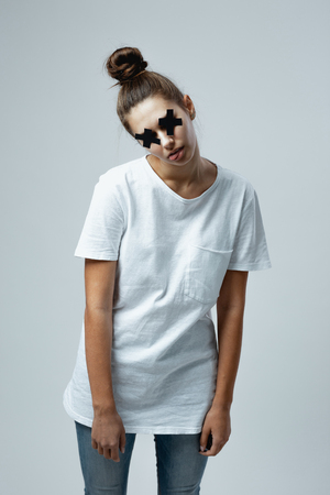 Young girl dressed in white t-shirt and jeans with black crosses of adhesive tape on the eyes stands on the white background in the studio like a zombie Stock Photo