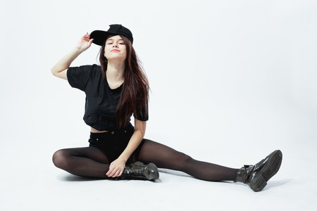 Funny young stylish girl dressed in a black top, shorts, tights and cap  sits on the floor  on the white background in the studio 스톡 콘텐츠