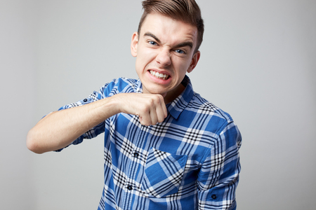 Aggressive  guy dressed in a plaid shirt is on a white background in the studio