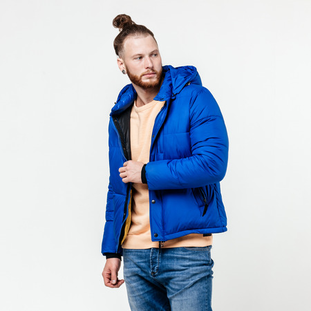 Fashionable man with beard and bun hairstyle dressed in yellow sweater, jeans and blue down jacket poses in the studio on the white background