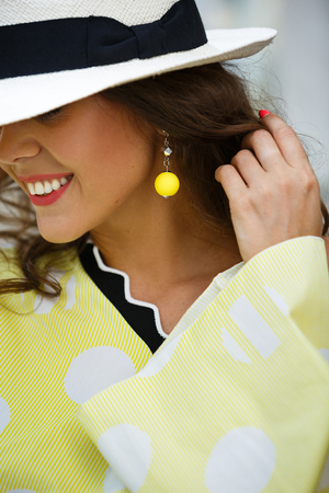 Portrait of a smiling brunette girl in a hat and yellow in white peas blues