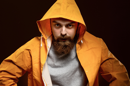 Red-haired guy with a beard and mustache dressed in a gray t-shirt and yellow jacket with a hood is posing on a brown background in the studio