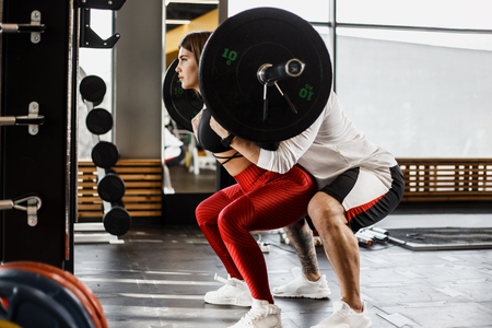 Athletic girl in stylish bright sports clothes doing back squats and strong athletic man helps her in the modern gym