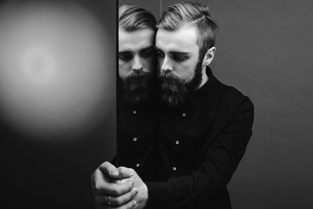 Black and white photo of a man with a beard and stylish hairdo dressed in the black shirt standing next to the mirror with his reflection