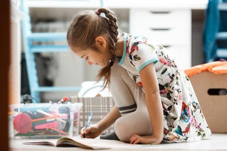 La bambina vestita con il vestito e le calze disegna nell'album seduta sul pavimento nella stanza
