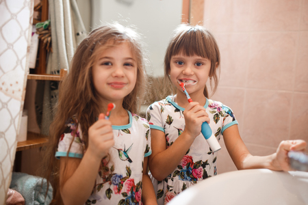 Two little nice sisters dressed in identical shirts brush their teeth in the bathroom Stockfoto