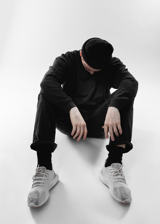 Guy dressed in black jeans, sweatshirt, hat and gray sneakers is sitting on the floor in the studio on the white background