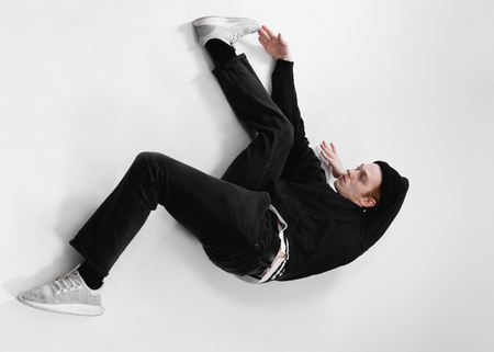 Freestyle dancer dressed in black jeans, sweatshirt, hat and gray sneakers is dancing lying on the floor in the studio on the white background Stock Photo