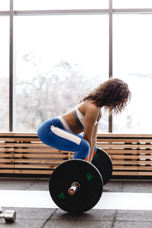 Slim curly dark-haired girl dressed in sports clothes is doing back squats with heavy barbell in the modern gym