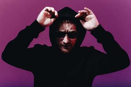 Portrait of fashion man in a black sweater with a hood and sunglasses in neon light in the studio