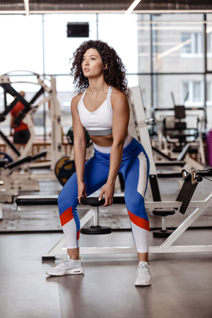 Pretty slim girl with dark curly hair dressed in a sportswear is doing back squats with heavy dumbbell in the modern gym with big window