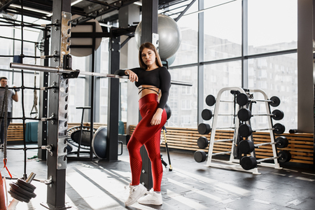 Slender girl in stylish bright sports clothes poses standing next to the horizontal bar with sport equipment around in the modern gym