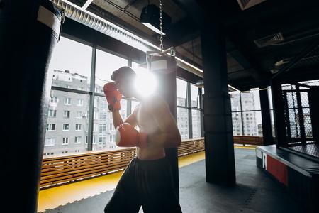 Un sportif en gants de boxe rouges avec un torse vêtu d'un short noir frappe un sac de boxe dans la salle de sport avec des fenêtres panoramiques