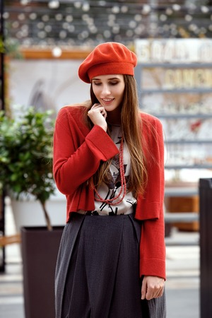 Fashionable girl dressed in a gray skirt, a red blouse on the t-shirt and red beret poses in the street on the sunny day