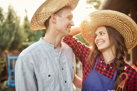 Happy guy and girl gardeners in a straw hats look at each other in the garden on a sunny day.