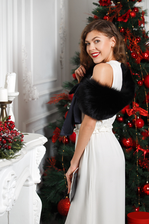 Beautiful stylish girl dressed in white dress and black fur mantle on it poses next to the New Year tree Stock Photo