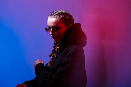 Portrait of fashion girl in a black sweater with a hood and sunglasses round shape in neon light in the studio