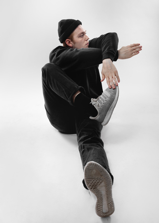 Freestyle dancer dressed in black jeans, sweatshirt, hat and gray sneakers is dancing sitting on the floor in the studio on the white background