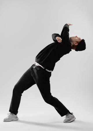 Guy dancer dressed in black jeans, sweatshirt, hat and gray sneakers is dancing in the studio on the white background