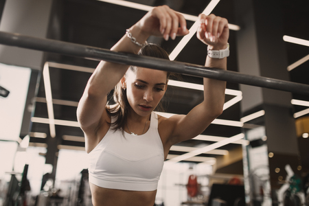 Athletic young brunet girl dressed in sportswear having rest next to the barbell in the modern gym