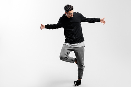 Stylish young dancer wearing a black sweatshirt and gray pants is dancing hip-poh