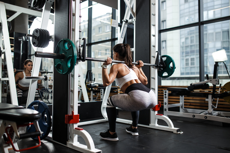 Young athletic girl dressed in sportswear squats with a barbell in the modern gym Stock Photo